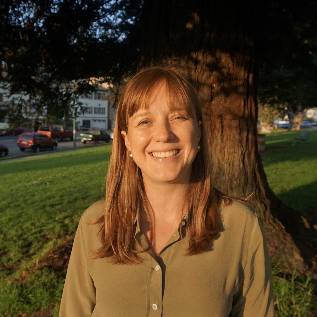White woman with strawberry blonde hair smiling in an olive shirt under a tree